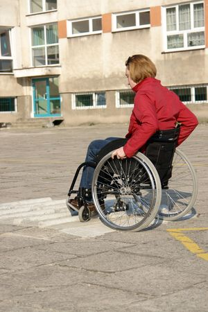 Handicapped woman practicing wheelchair ride over obstacle course for disabled photo