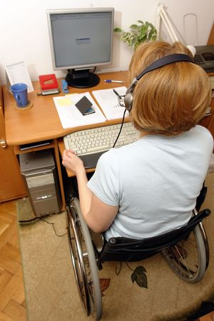Handicapped woman on wheelchair working at home as telemarketer photo