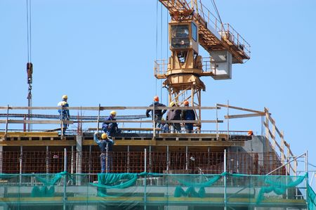 erecting: Group of construction workers working at building platform