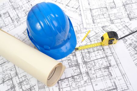Blue hard hat, yellow pencil, measuring tape and building plans photo