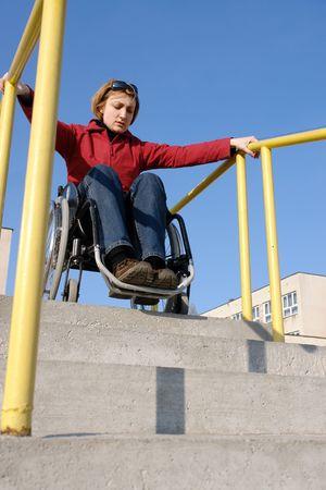 going down: Mujer a minusv�lidos en silla de ruedas bajando las escaleras concretas