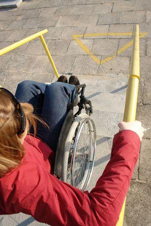 going down: Closeup de la mujer en silla de ruedas bajando las escaleras concretas