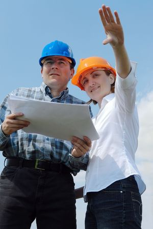 Young couple wearing helmets holding building project documentation visualizing their new future house photo
