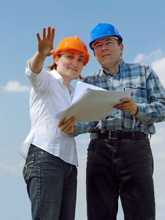 visualizing: Young couple wearing helmets visualizing their new future house based on their building project documentation Stock Photo