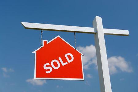 publicidad exterior: Pieza de madera de color blanco con rojo casa Vendido tabl�n de anuncios sobre cielo azul