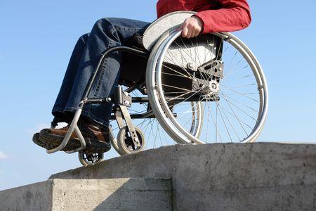 going down: Closeup de la mujer en silla de ruedas bajando el bordillo concretas