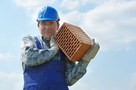 hollow: Construction worker in blue jumpsuit and helmet carrying hollow brick