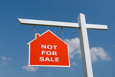 White wooden post with red house-shaped notice board spelling Not For Sale - over blue sky