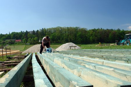 rafter: Man impregnating timber for rafter framing at the construction site