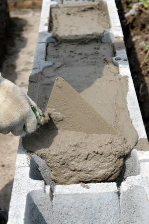 hollow wall: Closeup of mason hand spreading mortar with trowel in concrete shuttering blocks making house foundation