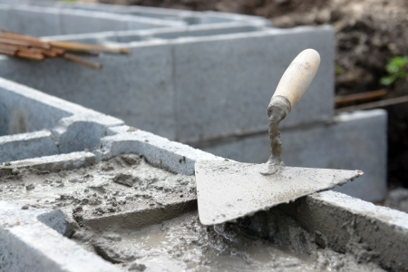 hollow wall: Closeup of masons trowel on concrete shuttering blocks filled with mortar