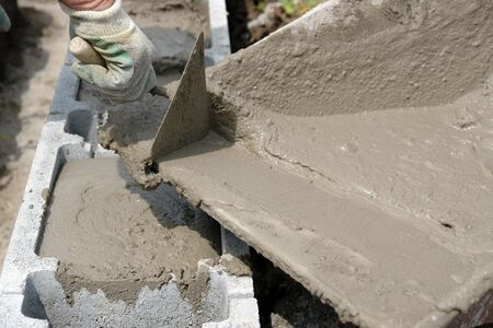 hollow wall: Closeup of mason hand pouring out mortar into concrete shuttering blocks from wheel-barrow Stock Photo