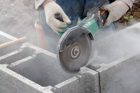 Construction worker making cuttings in concrete blocks for reinforcement using concrete cutter photo