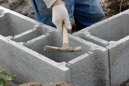 Construction worker hammering out cuts made in concrete blocks for placing reinforcement Stock Photo
