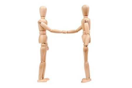 Two wooden dummies shaking hands over white background photo