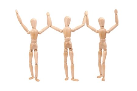 Three wooden dummies holding together hands up as winners isolated on white background Stock Photo - 3122713