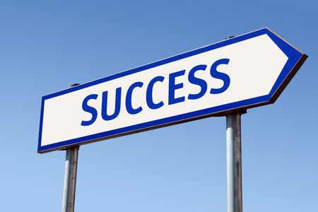 White metal directional roadsign with Success word over blue sky photo
