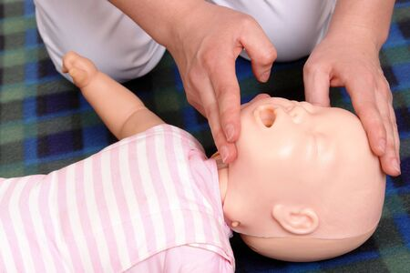 dummy first aid demonstration series - First aid instructor showing how to position  head before proceeding to mouth-to-mouth resuscitation photo