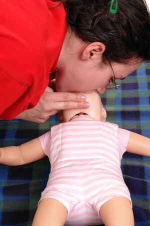 cpr:  dummy first aid demonstration series - first aid instructor demonstrating artificial respiration using  dummy