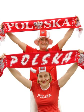 Two young female Polish soccer fans dressed in Polish national color t-shirts, caps and scarfs cheering on over white background photo