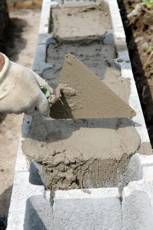 hollow wall: Closeup of mason hand spreading mortar with trowel in concrete shuttering blocks as house foundation Stock Photo