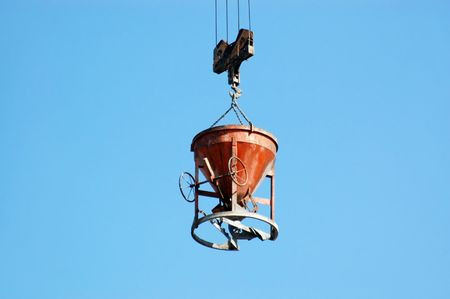 hopper: Charging hopper with concrete mix being transported by jib crane over blue sky Stock Photo