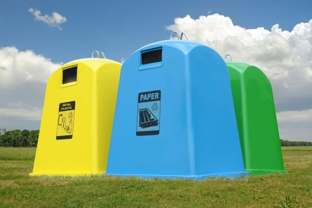 Recycle containers for paper, metal and plastic waste placed on grass over sky Stock Photo