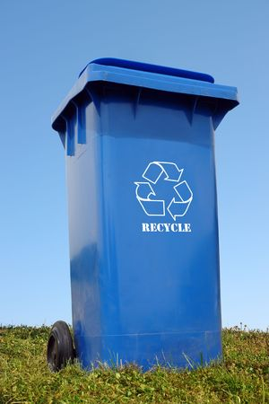 Blue plastic disposal bin with white recycle symbol in the grass over blue sky photo