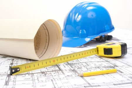 Blue hard hat, yellow pencil, measuring tape and building plans