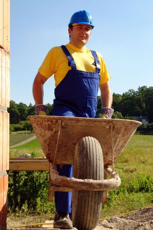 overall: Construction worker wearing blue overall and helmet with wheel-barrow Stock Photo