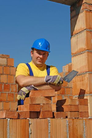 Construction worker wearing yellow t-shirt and blue helmet holding stainless steel trowel posing among unfinished brick house walls Stock Photo - 3256549