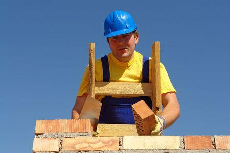 Mason in blue helmet building brick wall photo