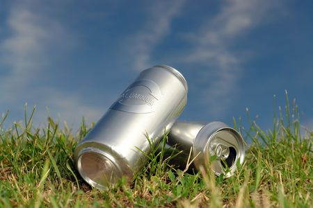 Two empty aluminum beer cans with recycle symbol laying in the grass over blue sky photo