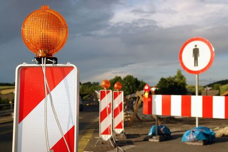 no access: Road works marked with red and white striped road warning posts with orange beacons and barrier with no access sign