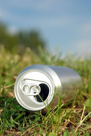 Lege aluminium bier kan tot in het gras Stockfoto