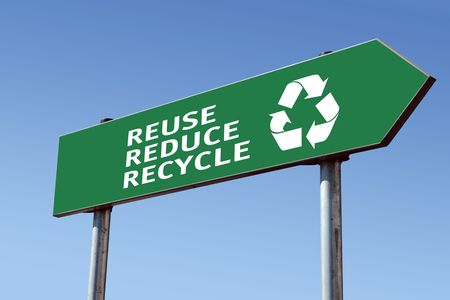 Green reduce-reuse-recycle directional roadsign over blue sky Stock Photo
