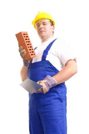 Construction worker wearing blue jumpsuit and yellow helmet holding stainless steel trowel and brick over white background photo