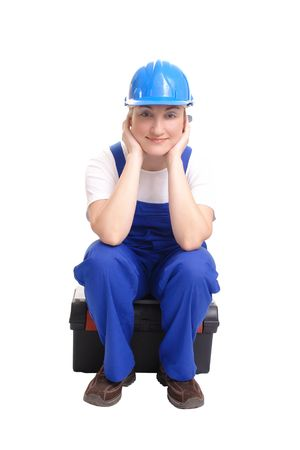 Female builder wearing blue helmet and jumpsuit sitting on toolbox, with content look over white background photo