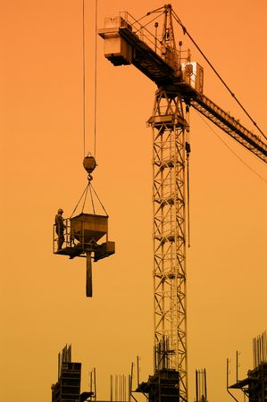 Silhouette of construction worker being transported by jib crane with concrete mix charging hopper againts sunset sky Stock Photo