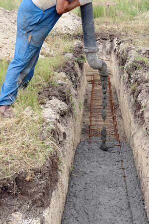 concrete pump: Closeup of construction worker injecting concrete mix into foundation excavation using concrete pump