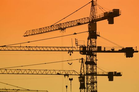jib: Jib crane silhouettes against sunset sky