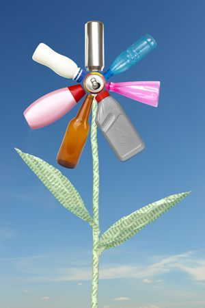 Recycle flower created from beer can, plastic and glass bottles and waste paper stem spelling reduce-reuse-recycle over blue sky photo