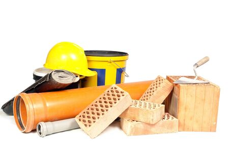 Perforated bricks, stainless steel trowel, yellow helmet insulation tar paper, sewage pipes and concrete primer bucket isolated on white Stock Photo - 3402115