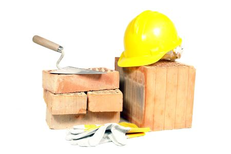 Perforated bricks, stainless steel trowel, yellow helmet and protective gloves isolated on white photo