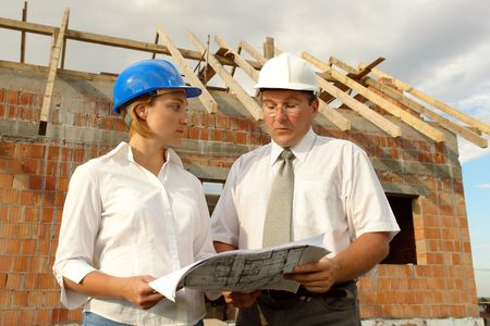 Female investor discussing building plans with the site manager against unfinished brick house with wooden roof structure photo