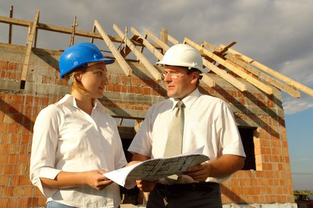 Female and male building designers discussing building plans against unfinished brick house with wooden roof structure