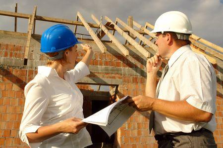 supervisi�n: Mujeres inversor discutir los planes de construcci�n con el administrador del sitio contra la casa de ladrillo sin terminar de madera con techo de estructura Foto de archivo