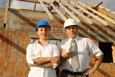 Female and male building designers wearing helmets posing over unfinished brick  with wooden roof structure photo