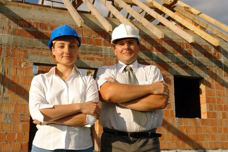 Female and male building designers wearing helmets posing over unfinished brick house with wooden roof structure photo