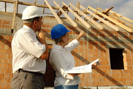 Female and male building engineers wearing helmets discussing building plans standing over unfinished brick house with wooden roof structure Stock Photo